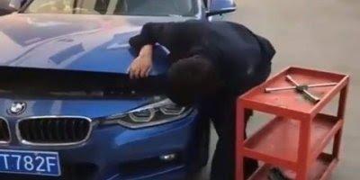 O que será que esta impedindo este rapaz de fechar o capô do carro?