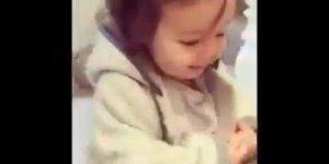 Criança se virando para colocar sapato e blusa de frio, linda!